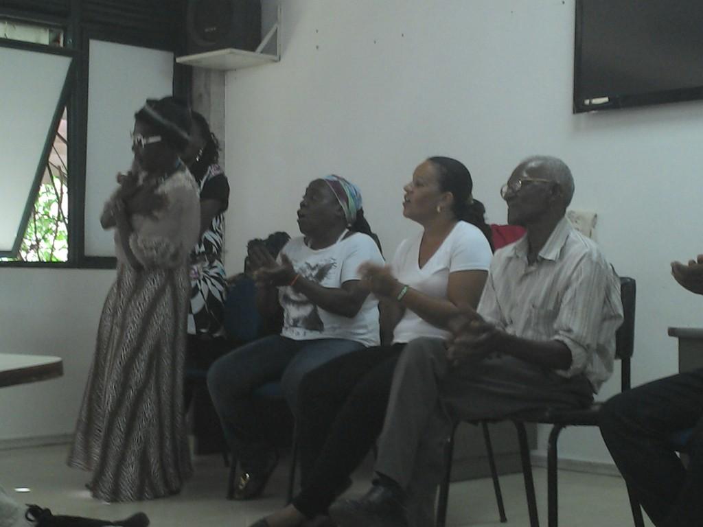 Mãe Tiana dança e canta para os professores e alunos na sala de aula, acompanhada pelos demais componentes da mesa.
