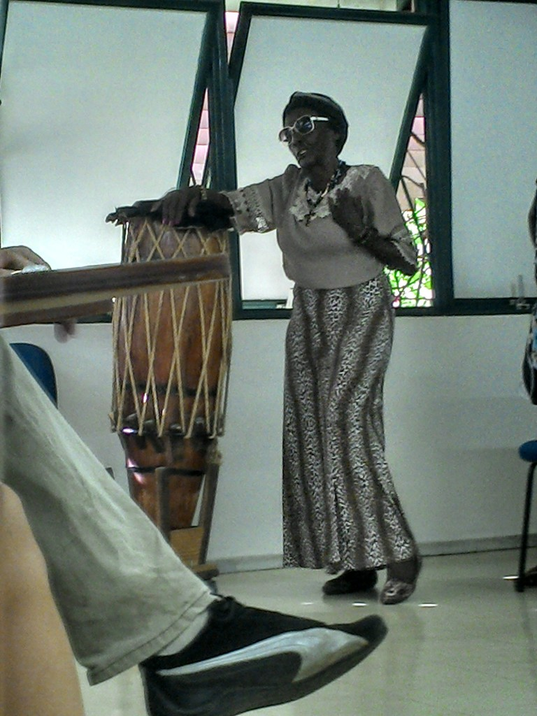 Dona Tiana fala à comunidade universitária sobre sua história, apoiada no instrumento musical que trouxe de sua comunidade.